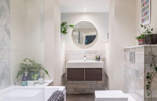 Badezimmer mit Kreisspiegel über Waschbecken